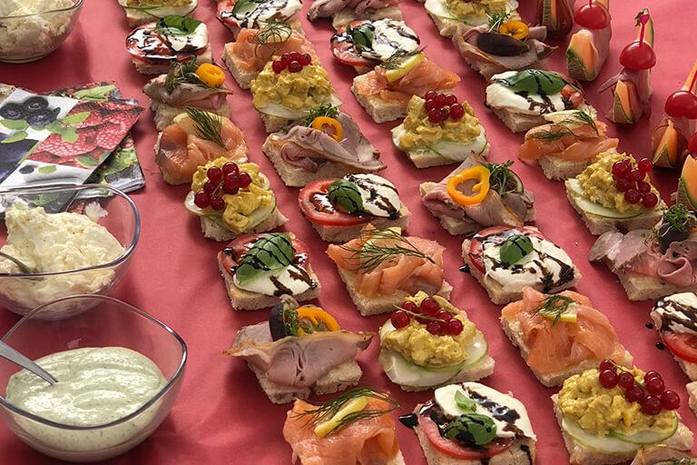 cirka 30 belegte brötchen mit lachs, eiaufstrich, mozzarella und tomaten kunstvoll garniert, diverse saucen links davon, catering vom bistro 54, ebensee