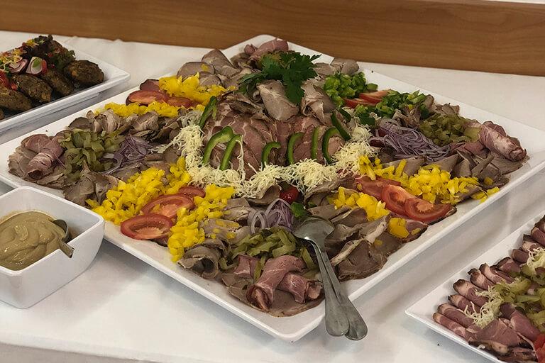 ansicht eines kalten buffets mit grossem fleischteller garniert mit paprika, tomaten, mais und kren, catering vom bistro 54, ebensee