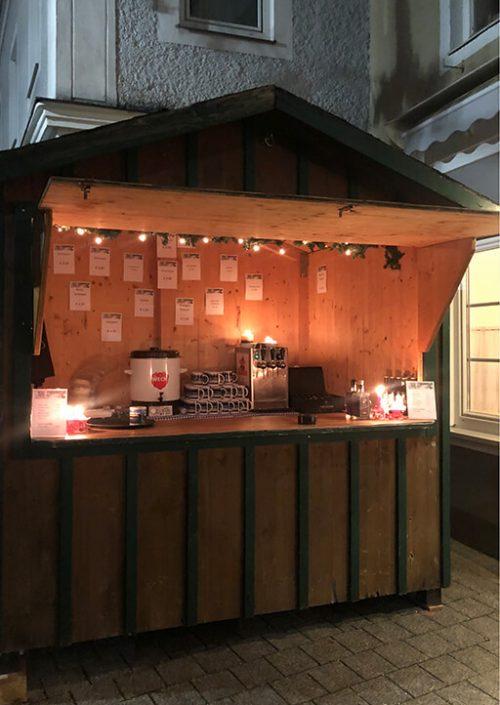 punschhütte aus holz beleuchtet vor bistro 54, marktgasse, ebensee